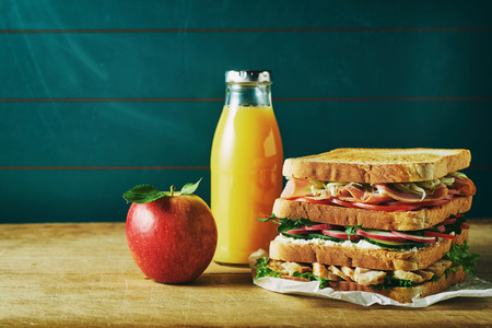 Lunch food set consist of sandwich, juice, apple on wooden table Stockfoto