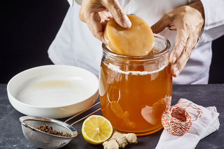Man placing the scoby or fungus in a glass jar of sweetened black tea to start the fermentation process to make kombucha Stock fotó