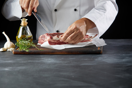 Chef wearing white coat cutting lamb chop with knife on cutting board Stock Photo