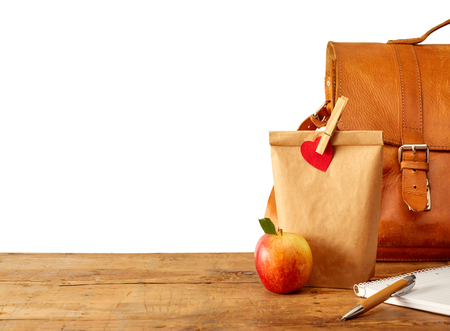 Brown bag lunch, fruit, notebook, pen and leather purse or backpack on table. Includes copy space over white.