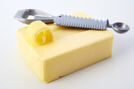 Pat of farm fresh butter with a partially cut curl on top and a metal butter curler or kitchen utensil in a food styling concept