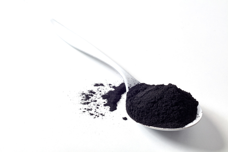 Spoon of round activated black natural plant charcoal in a spoon displayed on white with copy space used as a food and drink additive to detoxify the body Фото со стока