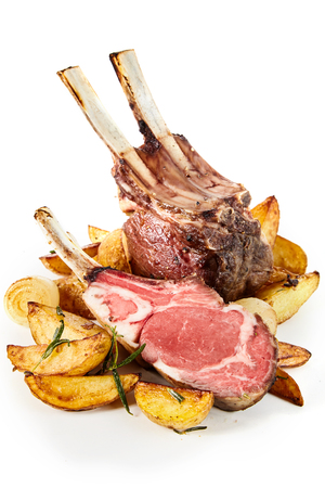 Roasted rack of lamb chops with sauteed wedges of rosemary potatoes cut through to show the tender marbled meat over white Stockfoto