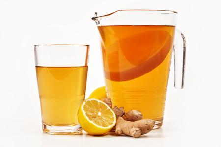 Jarra y vaso llenos de kombucha fresca hecha con té negro azucarado fermentado y servida con limón y raíz de jengibre sobre blanco visto desde el lateral