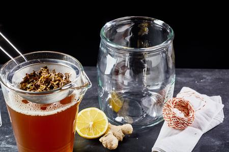 Preparing kombucha with tea, lemon and ginger in jar