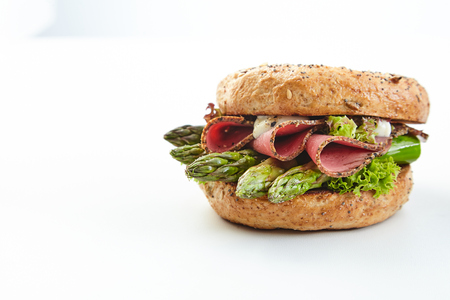 Speciality burger with fresh green asparagus tips with sliced ham and mayonnaise served on a bun over white with copy space