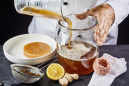 Man pouring filtered kombucha SCOBY tea into jar Banco de Imagens