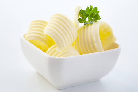 Elegant curls of fresh butter garnished with parsley in a small dish ready to be served at a formal dinner in a close up view Imagens