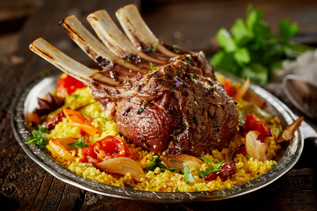 Oriental rack of lamb with saffron rice and roasted vegetables marinated and seasoned with spices and fresh herbs served on a platter Stockfoto