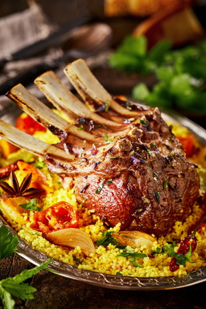 Gourmet seasoned Oriental rack of lamb with roast vegetables and saffron rice garnished with chopped parsley in a close up cropped view for a menu