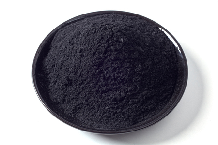 Shallow dish of ground activated black charcoal used as an additive in food and drink for detoxification over a white background