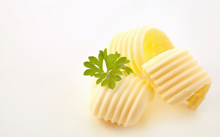 Three elegant curls of butter with fresh parsley on a white background with copy space alongside