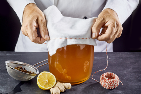 Man closing jar full of kombucha SCOBY tea with gauze bandage Stock Photo