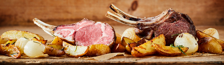 Panorama banner of grilled lamb chops with roasted seasoned potatoes and onions against a rustic wooden backdrop conceptual of a summer BBQ Banco de Imagens