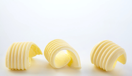 Border of three twirled butter curls made from fresh farm butter over white with copy space in a food styling concept