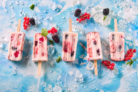 High Angle Still Life View of Five Iced Mixed Berry Yogurt Pops in a Row on Chilled Surface with Crushed Ice, Red Currants and Blackberries in front of Blue and White Background