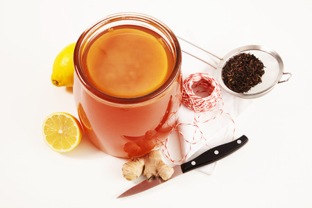 Jar of fresh Kombucha with ginger and lemon made from sweetened fermented black tea viewed high angle isolated on white