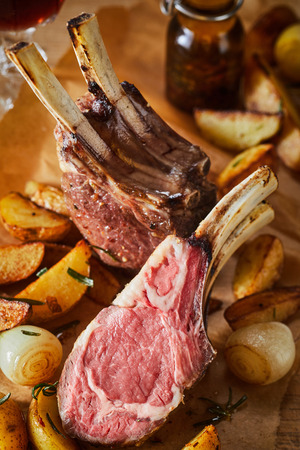 Tender barbecued rack of lamb with the chops cut through to show the tender medium rare meat served with roasted vegetables in a close up view for advertising or a menu