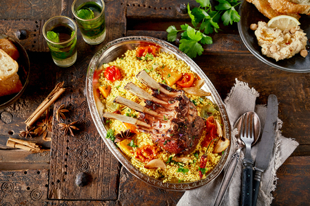 Portion of roasted lamb chops and saffron rice seasoned with fresh herbs and spices and served with roast vegetables in a top down view with ingredients on a rustic wooden table