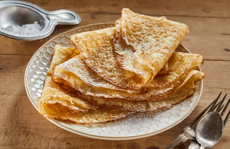 Crispy golden fried pancakes or griddle cakes on a plate dusted with castor sugar and stacked for a scrumptious breakfast or dessert 版權商用圖片