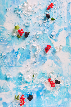 High Angle Still Life View of Blackberries, Red Currants, Mint Leaves and Crushed Ice on Blue and White Abstract Background
