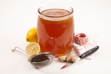 Glass jar of fermented sweetened Kombucha tea surrounded with fresh lemon and root ginger for flavoring, tea strainer with leaves, knife and string isolated on white