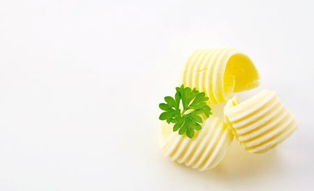 Three decorative elegant curls of farm fresh butter garnished with parsley arranged to the side on white with copy space in wide angle format