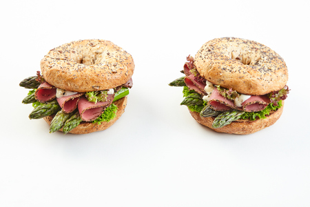 Speciality asparagus burgers with parma ham, lettuce and mayonnaise on fresh buns over white with copy space Stock Photo