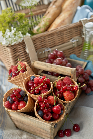 Fresh red berries in ice cream cones displayed upright in an old wooden box at a picnic with red currants, raspberries, strawberries, blueberries and cherries 写真素材