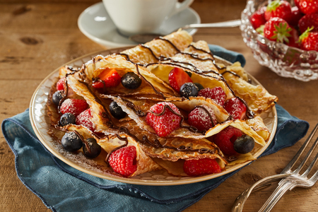 Plated freshly made golden berry pancakes filled with raspberries, strawberries and blueberries dusted with sugar and drizzled with chocolate
