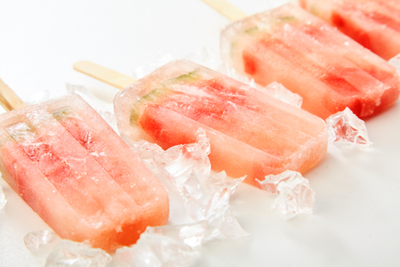 Fresh homemade fruit frozen popsicles with watermelon laid out in a diagonal receding row on crushed ice for a healthy summer snack