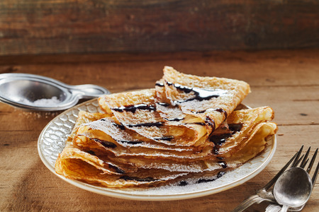 Serving of crispy golden fried batter pancakes or griddle cakes dusted with sugar and topped with chocolate sauce on a wood table with copy space