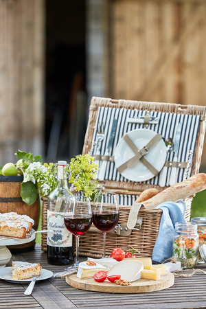 Vintage picnic hamper with wine, bread, cheese platter and freshly baked tart for dessert on a table in the garden