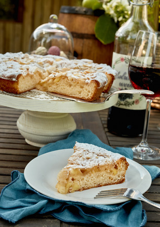 Delicious fresh cake for dessert at a picnic sliced and served on a plate with glasses of red wine on a garden table