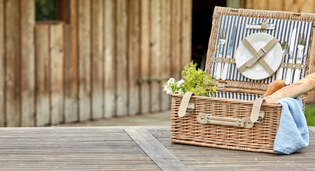 Open vintage fitted picnic hamper with baguettes outdoors on a rustic table near a wooden cabin with space alongside for placement of food in panorama format