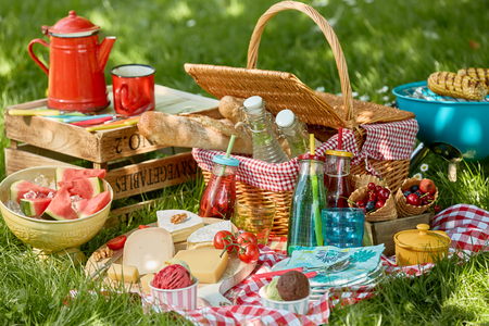 Country barbecue or picnic in a spring meadow with corn on the grill, cheese, bread assorted fresh fruit, soft drinks and a colourful red coffee can on a crate