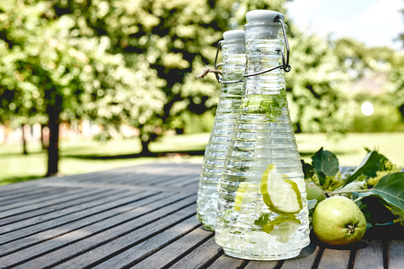 Refreshing infused water with apple slices outdoors on a rustic wood picnic table overlooking a park 版權商用圖片