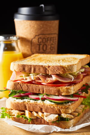 Thick tasty fresh sandwich with ham and vegetables against cup of coffee 版權商用圖片