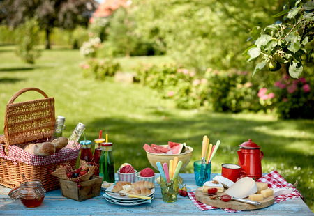 Empty summer park background with picnic arrangement of bread, fruit, italian ice and coffee