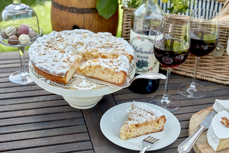 Sliced freshly baked cake or tart for a picnic dessert served on a wooden outdoor table with glasses of red wine and chocolate bonbons Stock Photo