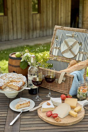 Selection of cheese on a platter with red wine served on an outdoor table with a picnic hamper and a freshly baked sliced cake for dessert