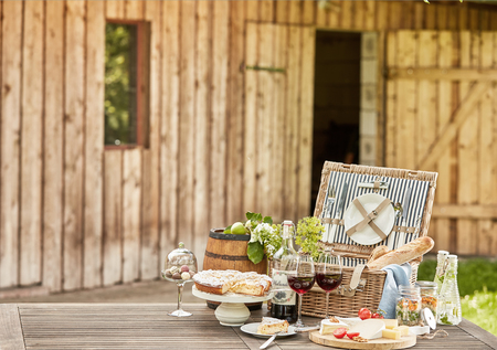 Gourmet picnic hamper served al fresco on a rustic garden table in front of a wooden cabin with cake, cheese platter, pickles baguettes and red wine, copy space alongside