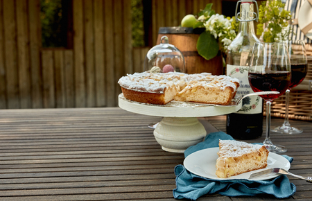 Close Up of Slice of Cake on Plate Beside Pedestal and Two Glasses of Red Wine in front of Picnic Basket on Wooden Table in Outdoor Garden with Copy Space