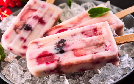 Close up of a healthy frozen yogurt and mixed berry popsicle on a bed of crushed ice in a bowl for menu advertising Standard-Bild