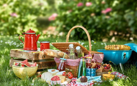 Picnic basket next to small grill and wooden box with foreground picnic blanket covered in food and drink sitting on green grass in summer