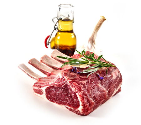 Uncooked rack of lamb with a fresh sprig rosemary for flavoring and decanter of olive oil isolated on white in square format