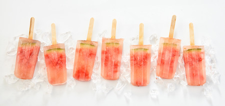 Line of frozen watermelon popsicles or lollies made with fresh tropical summer fruit on a bed of ice in a flat lay panorama still life Zdjęcie Seryjne - 106187167