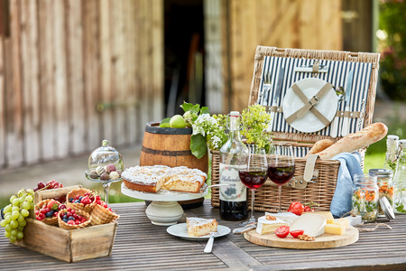 Tasty summer picnic al fresco on a garden table with red wine, fresh berries and fruit, cheese platter, baguettes, pickles and cake for dessert Stock fotó