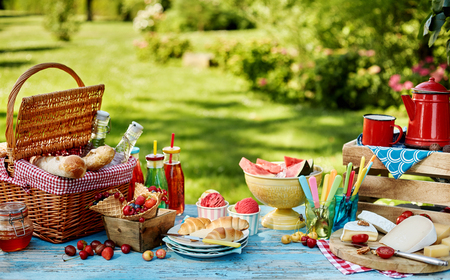 Exquisite summer picnic scene with bread basket, plates of fruit and coffee on table. Includes copy space