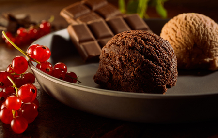 Close Up Still Life of Scoops of Gourmet Chocolate Ice Cream Garnished with Red Currants and Chocolate Bar Squares in Large Dish